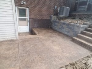Stamped concrete patio, precast concrete steps, retaining wall rebuild. raised air conditioner and installed new drainage.