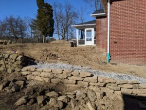 Rebuild of existing retaining wall using natural stone.