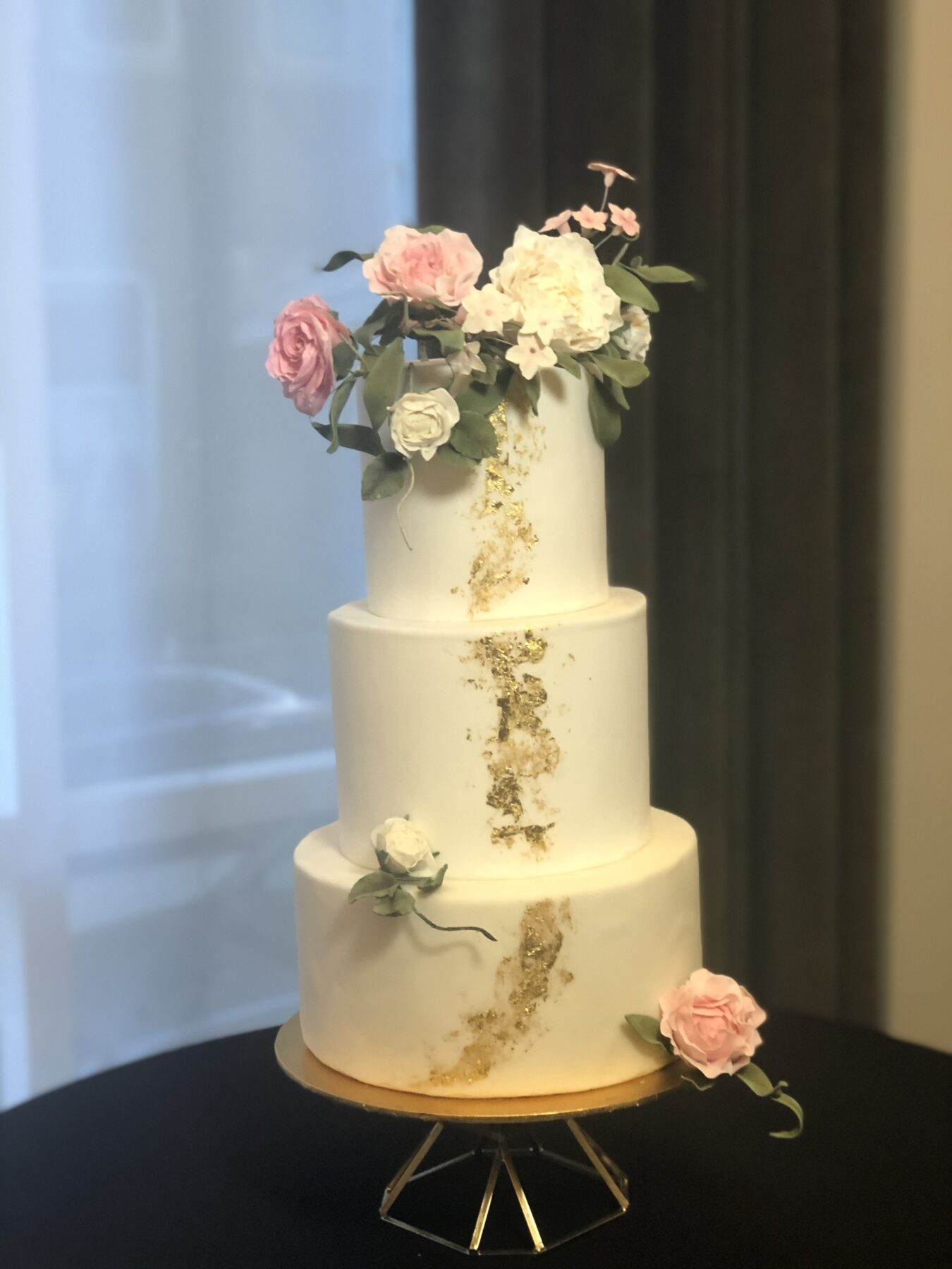 Elegant wedding cake white fondant with gold leaf running down the front, fondant flowers,